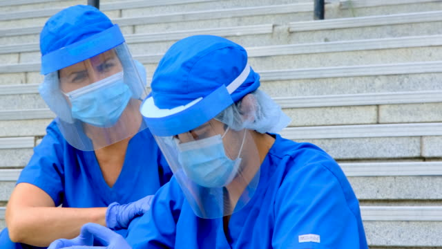 Tired, overworked, exhausted health care workers sitting outside the hospital while taking a break Tired, overworked, exhausted health care workers sitting outside the hospital while taking a break shield stock videos & royalty-free footage