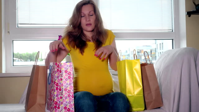 Tired pregnant woman with colorful bags sit on sofa back home after shopping video