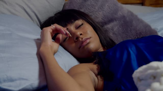 Tired restless woman suffering a nightmare in bed Attractive restless african american woman in pajamas suffering a nightmare, making nervous hand moves while lying in bed at night. Stressed female with sleeping disorder sleeping in bed at home. shivering stock videos & royalty-free footage