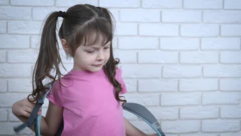 vidéos et rushes de écolier fatigué avec un sac à dos. - lourd