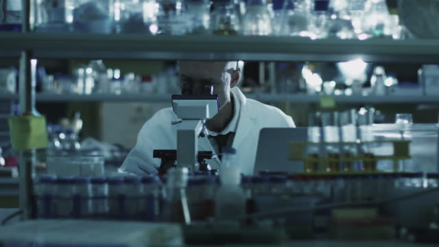 Tired senior male scientist is working with a microscope in a laboratory. video