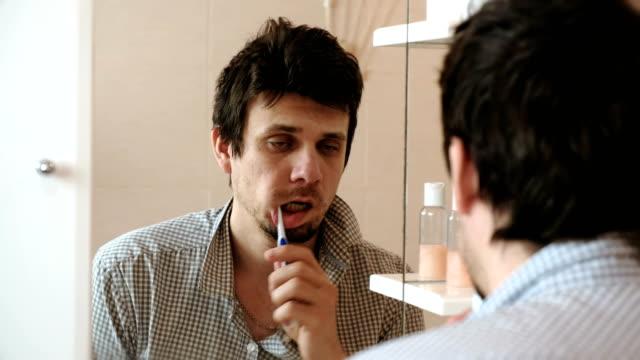 vídeos y material grabado en eventos de stock de cansado hombre sueño con una resaca que se a despertado cepillo los dientes, mira su reflejo en el espejo. - crudo