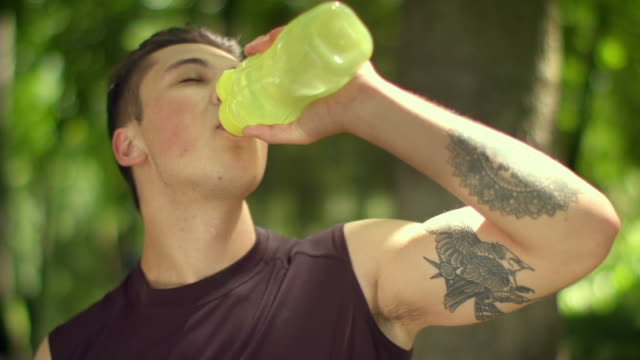 Tired sport man drinks water from plastic bottle after marathon in park video