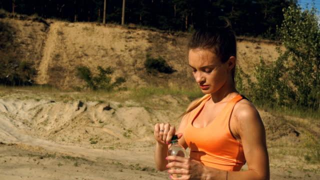 疲れてスポーツ女性ハード トレーニング後水を飲む - 女性選手点の映像素材/bロール