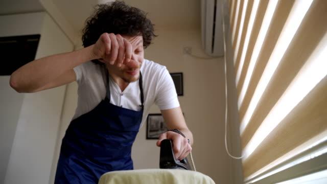 vídeos y material grabado en eventos de stock de cansado estancia en casa padre planchando la ropa en casa - padre que se queda en casa