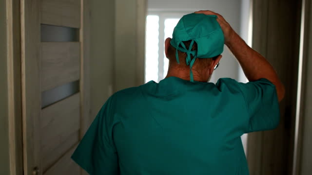Tired surgeon after the operation. A man in a medical gown walks along the corridor, sits on a chair and takes off his hat. Surgeons hands close-up. Medical error