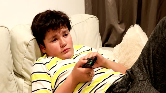 Tired teen lying on sofa and watching tv at home 12 years old child boy watching tv sitting on a couch at home alone laziness stock videos & royalty-free footage