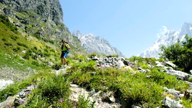 turista stanco scende dalla montagna dopo aver superato il percorso, chiude la telecamera con la mano. l'uomo con uno zaino torna dalle montagne. - dorso umano video stock e b–roll