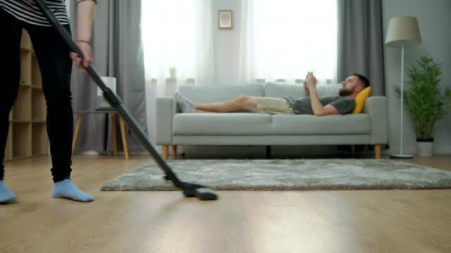 Tired wife vacuuming parquet floor and her husband play on smartphone on sofa video