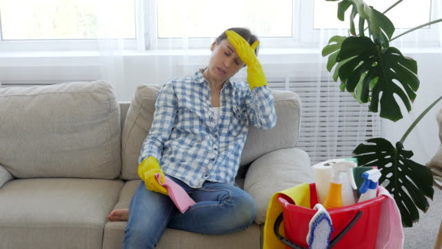 Tired woman after cleaning the house sitting on the sofa Close-up of tired woman after cleaning the house sitting on the sofa. Female relaxing on the settee chores stock videos & royalty-free footage