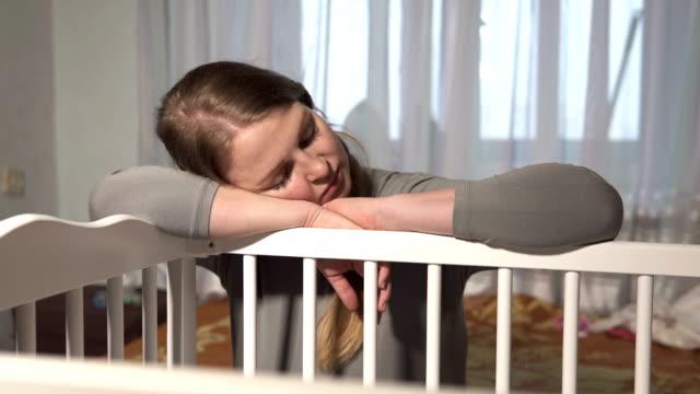 Tired woman fell asleep near the crib of a newborn daughter video