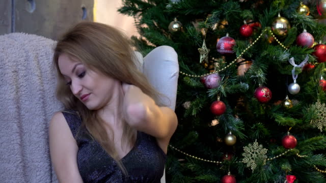 Tired woman having pan in neck on christmas tree background video