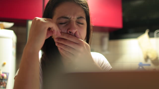 Tired woman in front of computer screen yawning with hand in mouth. Casual candid authentic 4K yawn clip of 30 year old girl exhausted in front of laptop Tired woman in front of computer screen yawning with hand in mouth. Casual candid authentic 4K yawn clip of 30 year old girl exhausted in front of laptop yawning stock videos & royalty-free footage