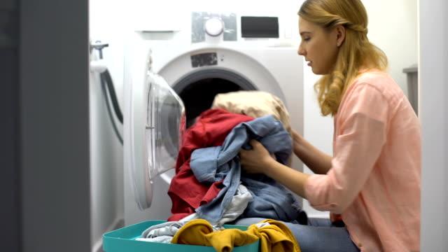 vídeos y material grabado en eventos de stock de mujer cansada cargando ropa en lavadora, molesta con la rutina de las tareas domésticas - tareas domésticas