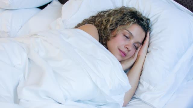 vídeos y material grabado en eventos de stock de mujer cansada de dormir en la cama - colchón
