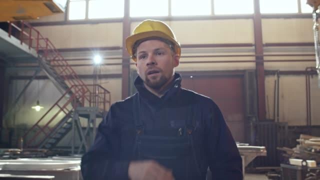 Tired Worker Walking through Metal Fabrication Plant