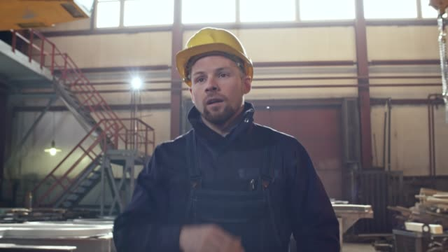 tired worker walking through metal fabrication plant - irriducibilità video stock e b–roll