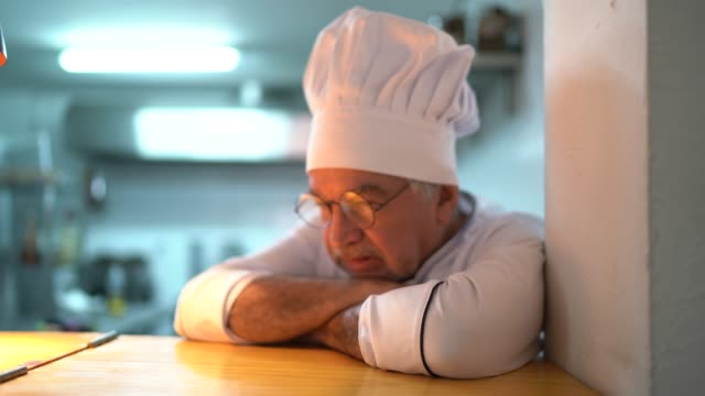 A tired / worried senior chef in the kitchen counter