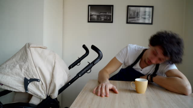 Tired young father drinking coffee and trying to stay awake-humor concept video
