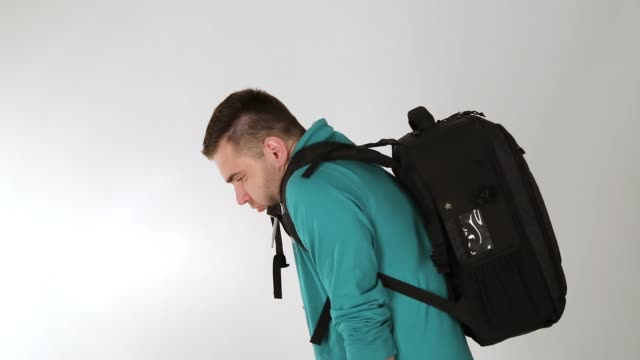 Tired young man taking of backpack, back pain, studio shot, white background