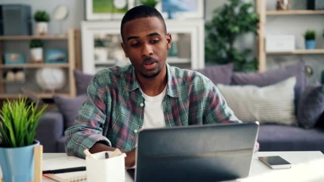 vídeos de stock, filmes e b-roll de o homem novo tired que usa o portátil e o bloco de notas têm o esforço ao trabalhar em casa - distante