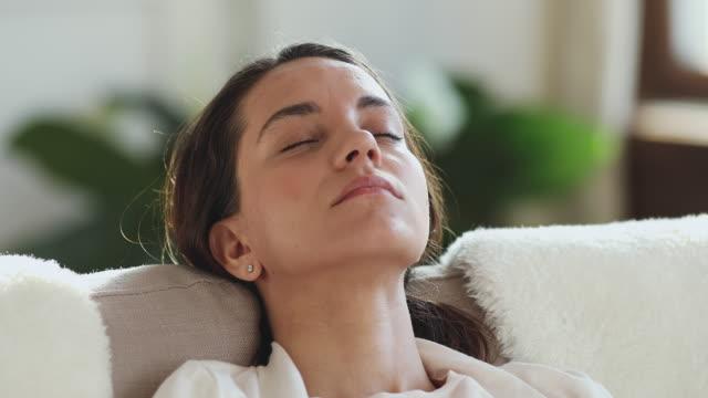 vidéos et rushes de jeune fille de race mélangée fatiguée s'est endormie sur le divan confortable. - se reposer