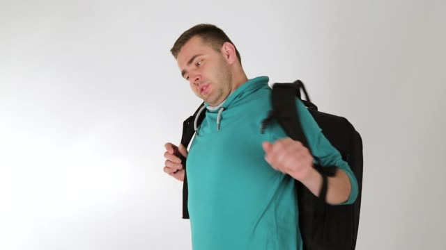 Tired young taking a break, wearing backpack, back pain, studio shot, white background