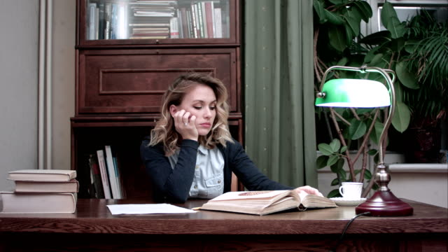 Tired young woman falling asleep over a book while sitting at the table video