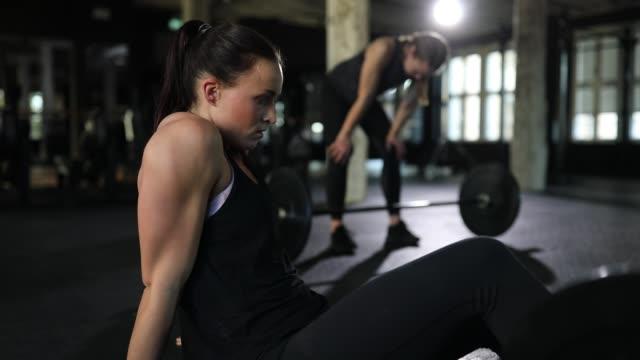 vídeos de stock e filmes b-roll de tired young women relaxing after workout at gym - dureza