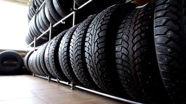 Tires for wheels in the auto parts store Large stand with wheel tires in an auto parts store tires stock videos & royalty-free footage