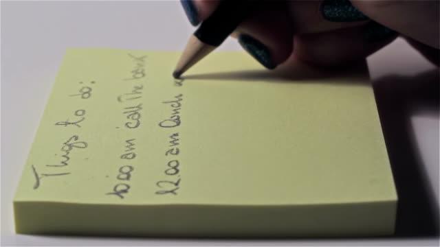 att göra-lista: kvinna skriva med en penna hennes utnämningar av dagen - helgaktivitet bildbanksvideor och videomaterial från bakom kulisserna