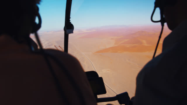 CU to MS Helicopter pilot and passenger flying over Deadvlei dessert,Namibia,Africa Helicopter pilot and passenger flying over Deadvlei dessert,Namibia,Africa. Zoom In,Zoom Out,shaky,Real Time. Shot in 8K resolution. extreme terrain stock videos & royalty-free footage