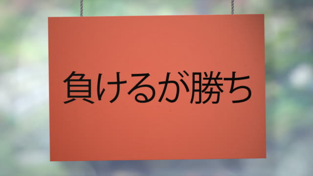 To lose means to win cardboard Japanese sign hanging from ropes. Luma matte included so you can put your own background.