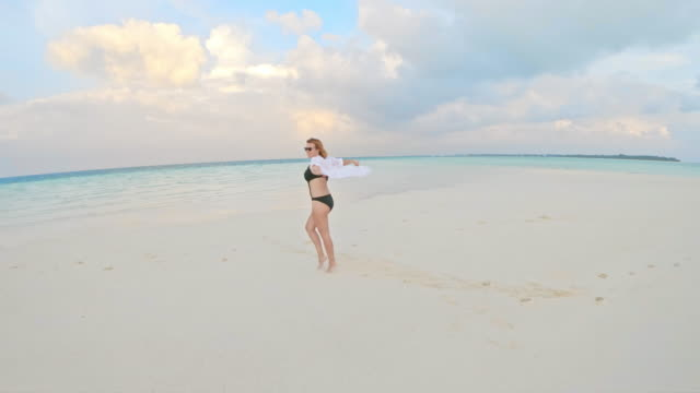 CU to MS Woman holding seashell on tropical ocean beach,Maldives CU to MS Woman holding seashell on tropical ocean beach,Maldives. Pan Up,Tilt Down, indian ocean stock videos & royalty-free footage