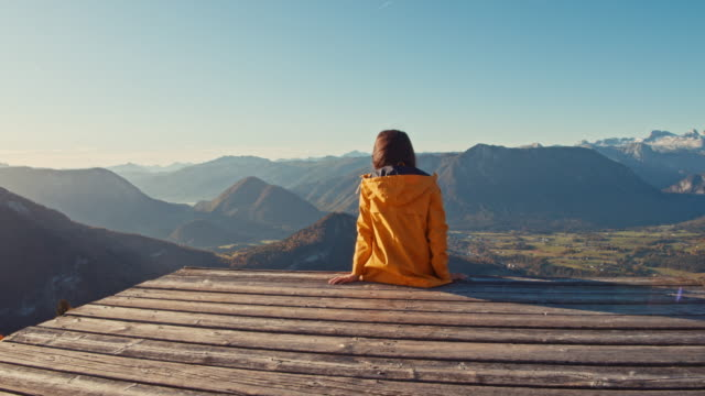 CU to MS Young woman sitting at edge of platform, enjoying sunny scenic mountain view, Loser Mountain, Austria