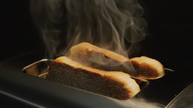 vídeos de stock e filmes b-roll de toast gets burnt and smokes in the toaster. slow motion. filmed on red camera. forgetful, late and problem concepts. - burned cooking