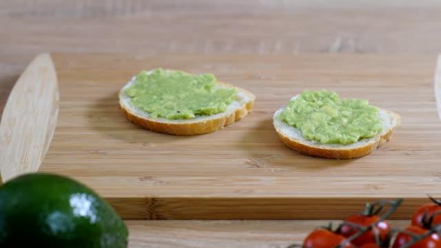 stockvideo's en b-roll-footage met toast met avocado, cherry tomaat en vlas zaden op rustieke houten achtergrond. gezond ontbijt. - geroosterd brood