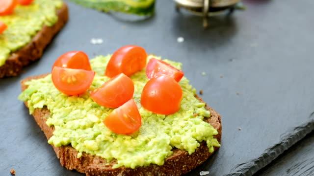 toast mit avocado, tomaten und gewürzen - vollkorn stock-videos und b-roll-filmmaterial