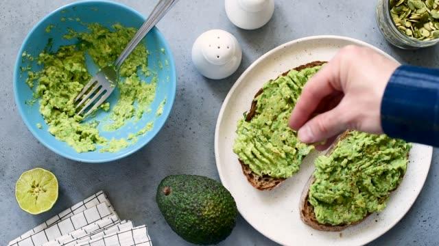 stockvideo's en b-roll-footage met toast met puree avocado, koriander en pompoenpitten - geroosterd brood