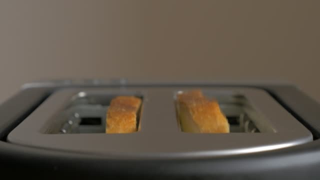 toasting bread in toaster machine close-up 4k 2160p uhd footage - making toast in toaster with two bread slices 4k 3840x2160 uhd video - zły stan filmów i materiałów b-roll