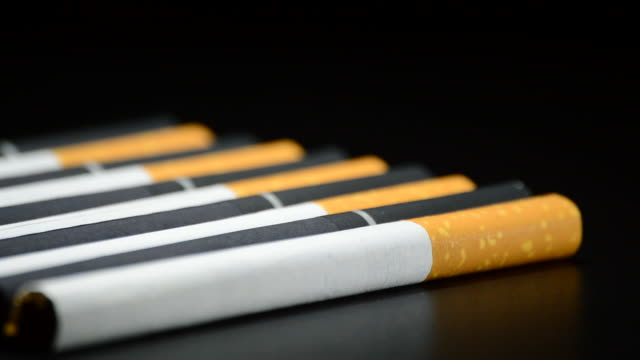 Tobacco cigarettes rotating on black background video
