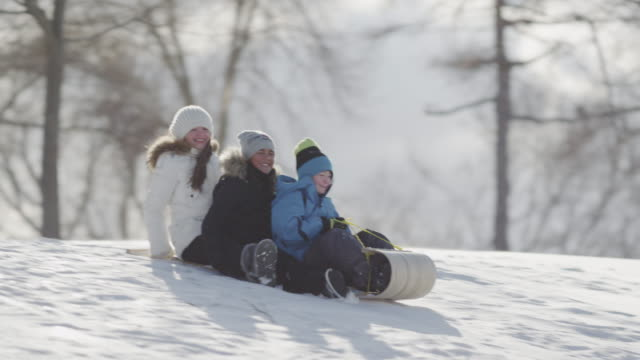 Tobogganing on a hill with friends video