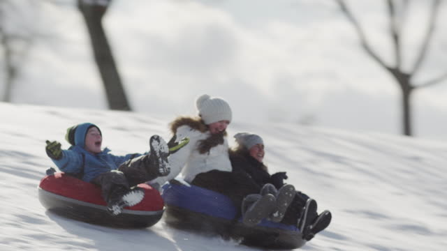 Tobogganing on a hill with friends Winter fun outside sledding down a hill with friends. recreational pursuit stock videos & royalty-free footage