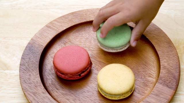 Toddler and parent's hand picking Macarons.