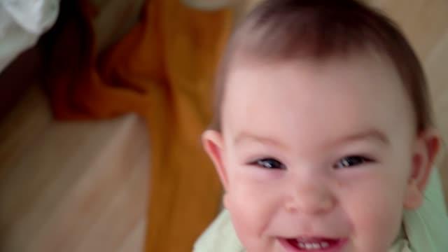 vídeos de stock, filmes e b-roll de o bebê da criança perto dos pés das matrizes quer levantar o uo e sentar-se em braços, conceito feliz do união - novo bebê