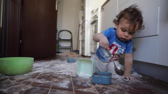 Toddler boy having fun with flour at kitchen