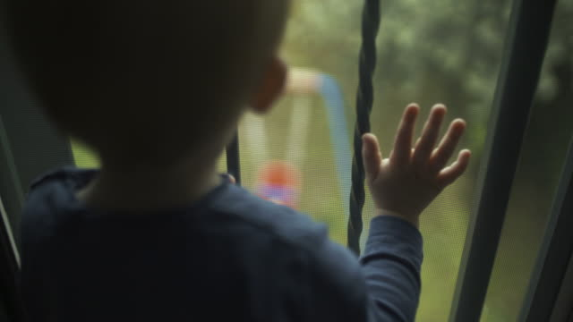 toddler boy looking out the window. shot in slow motion - neonati maschi video stock e b–roll