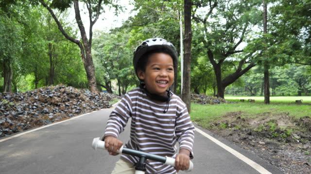 vídeos de stock, filmes e b-roll de scooter da equitação do menino da criança - criança pequena