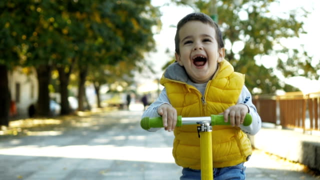 Toddler boy riding scooter Cute, little boy riding scooter and smiling. one boy only stock videos & royalty-free footage