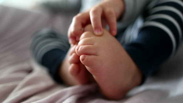 Toddler boy touchign toes. one year old Infant child baby feet